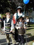 Mother and 2 boys in period costume, the small boy is trying on the Sealed Knot's English Civil War armour